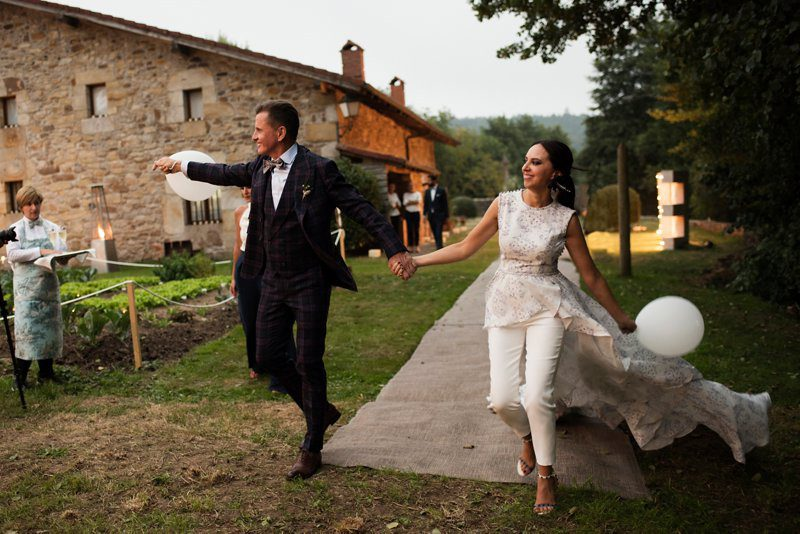 Alicia Rueda on her wedding day walking hand in hand with her husband